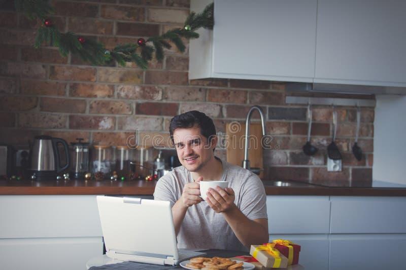 Человек с чашкой чаю или кофе и портативным компьютером стоковое фото