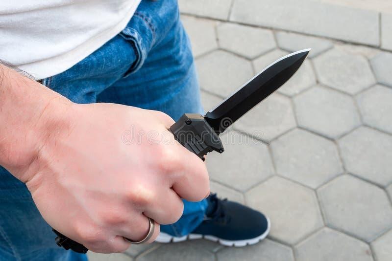 Человек с черным карманом вне передний нож в его руке стоковые изображения rf