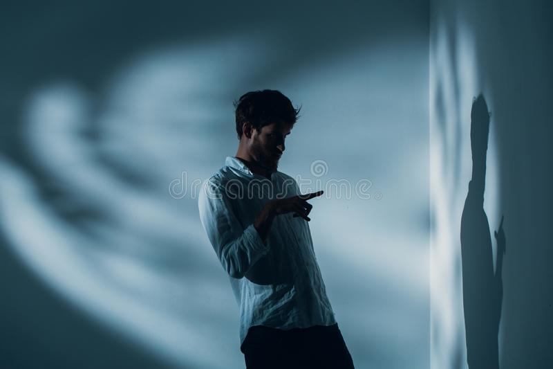 Человек с шизофренией стоя самостоятельно в комнате указывая на его тень на стене, реальном фото стоковые изображения rf