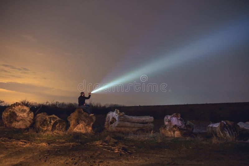 Человек с электрофонарем вечером стоковые фотографии rf