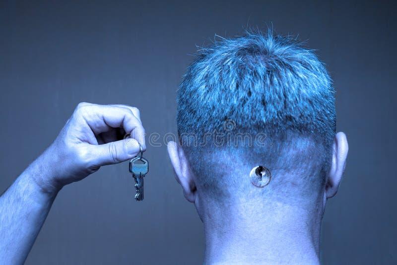 Человек с keyhole позади его головы держит ключи в поднятой руке стоковое изображение rf