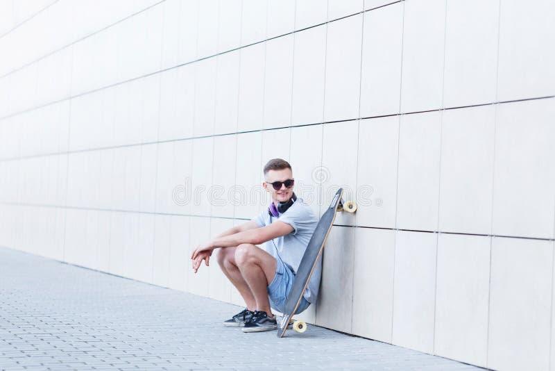 Человек с Longboard перед стеной стоковое изображение rf