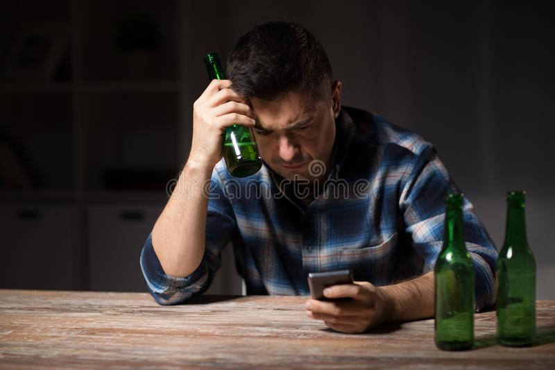 Человек с smartphone и бутылкой пива на ноче стоковая фотография rf