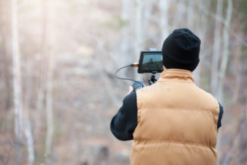 Человек с videocamera снимая лес в осени стоковые изображения
