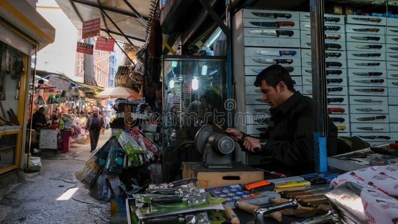 Человек точит нож на базаре стоковые изображения rf