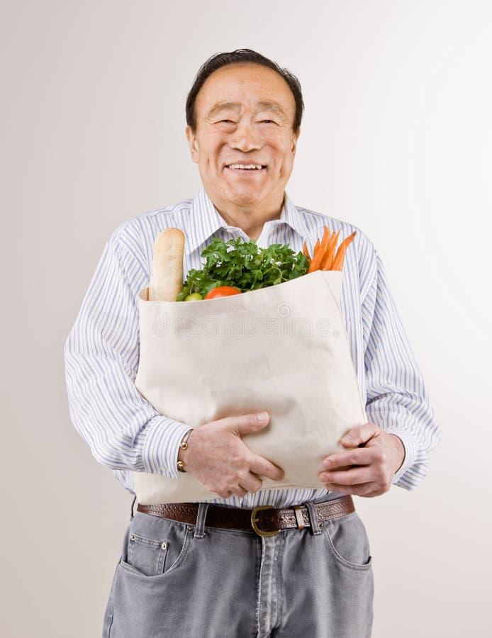 человек удерживания бакалеи свежих фруктов мешка полный стоковое изображение rf