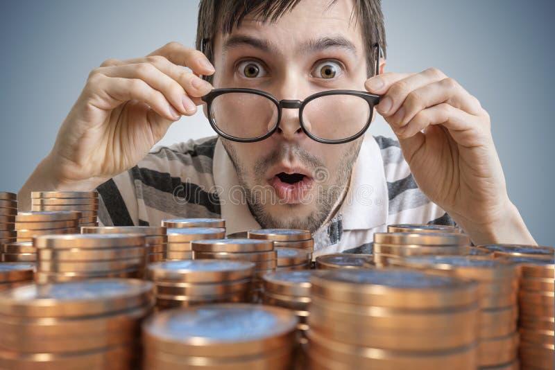 Человек удивленный детенышами выигрывает деньги Много монетки в фронте стоковое фото rf