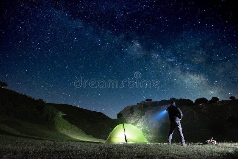 Человек указывая голубой электрофонарь на гору под звездным небом в парке Nebrodi стоковые фото