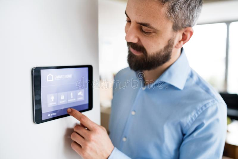 Человек указывая к таблетке с умным главным экраном дома стоковое фото