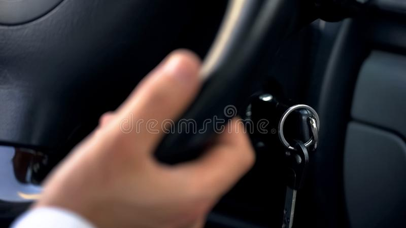 Человек управляя автомобилем, держа руку на колесе, конец вверх на ключах, транспорте стоковая фотография rf