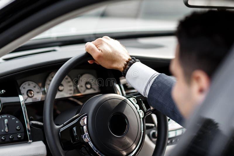 Человек управляя роскошным автомобилем стоковое фото