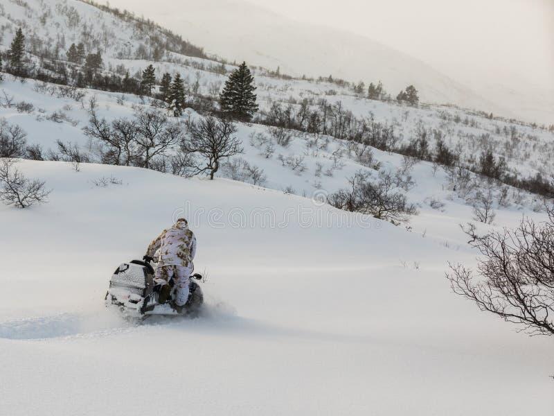 Человек управляя снегоходом в снеге стоковое изображение rf
