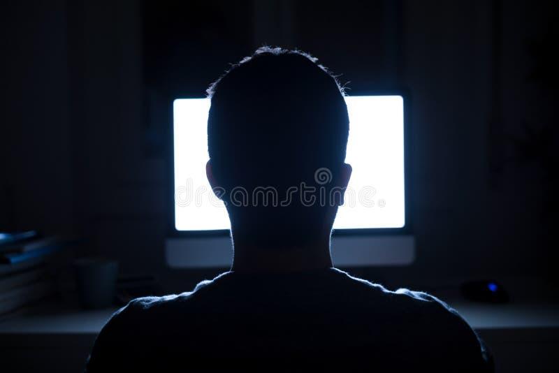 Человек усаженный перед монитором компьютера на ноче стоковое изображение rf