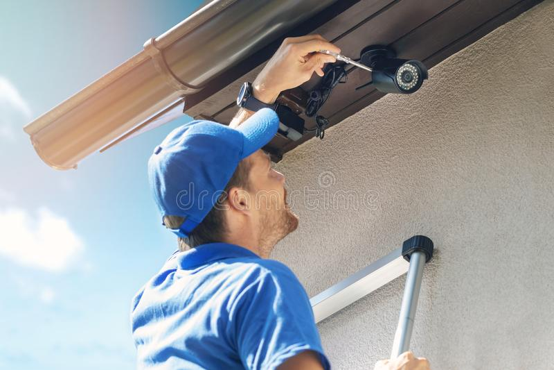 Человек устанавливает внешнюю камеру ip наблюдения для домашней безопасности стоковые изображения rf