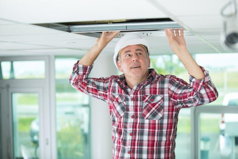 Человек устанавливает приостанавливанный потолок в дом стоковые изображения rf