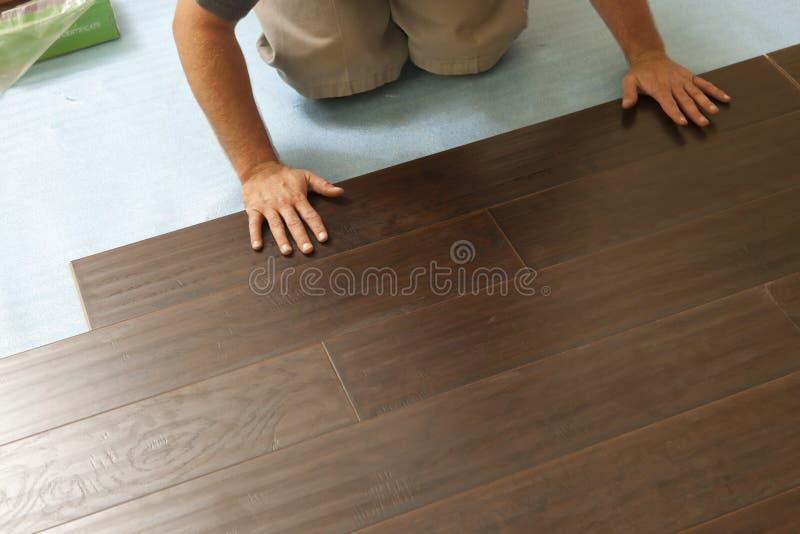 Человек устанавливая новый прокатанный деревянный настил стоковое изображение