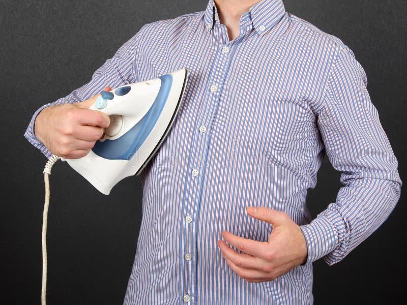 Человек утюжит его рубашку на его комоде стоковое фото