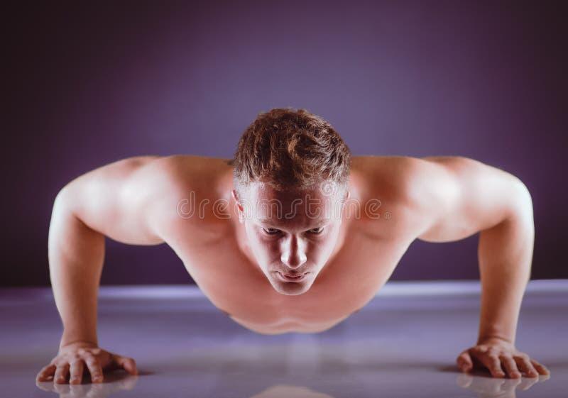 Человек фитнеса делать нажимает поднимает на поле стоковые фото