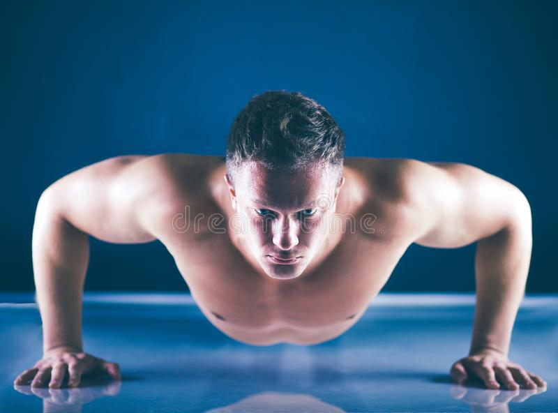 Человек фитнеса делать нажимает поднимает на поле стоковое фото