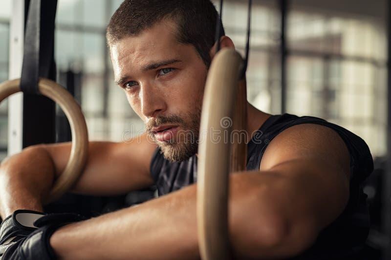 Человек фитнеса молодой полагаясь и отдыхая на спортзале стоковые изображения rf