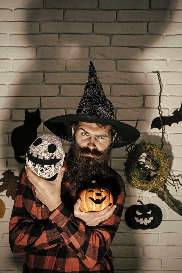 Человек хеллоуина в тыкве удерживания шляпы волшебника и голове призрака стоковые изображения rf