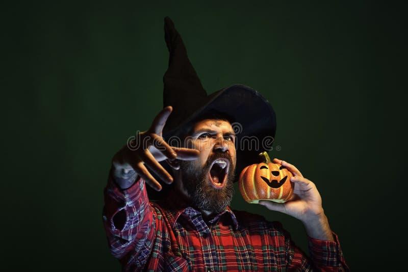 Человек хеллоуина в тыкве удерживания шляпы волшебника стоковое фото