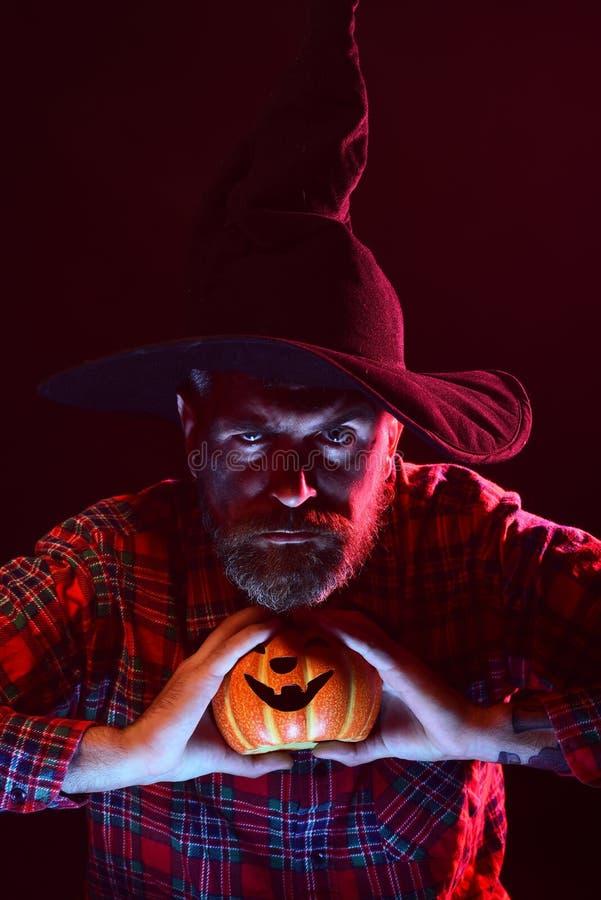 Человек хеллоуина в шляпе ведьмы держа тыкву в темноте стоковые изображения rf