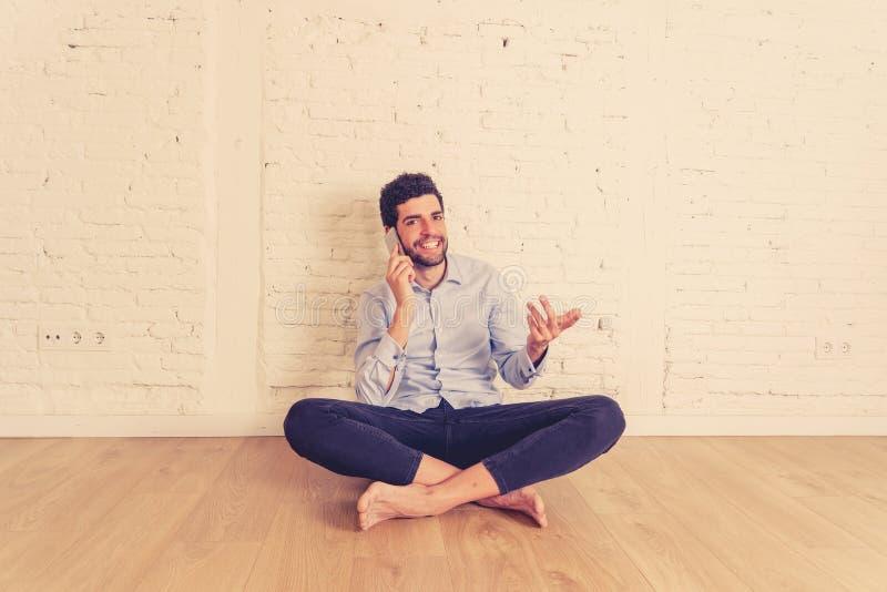 Человек хипстера молодой говоря на мобильном телефоне счастливом в его новой пустой квартире гордой его вклада стоковое изображение