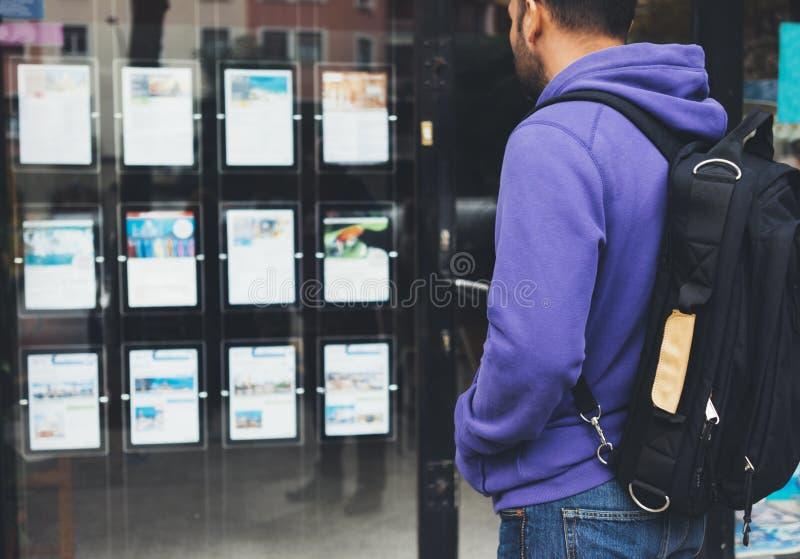 Человек хипстера молодой с рюкзаком и карта смотря гостиницу плаката p стоковое изображение