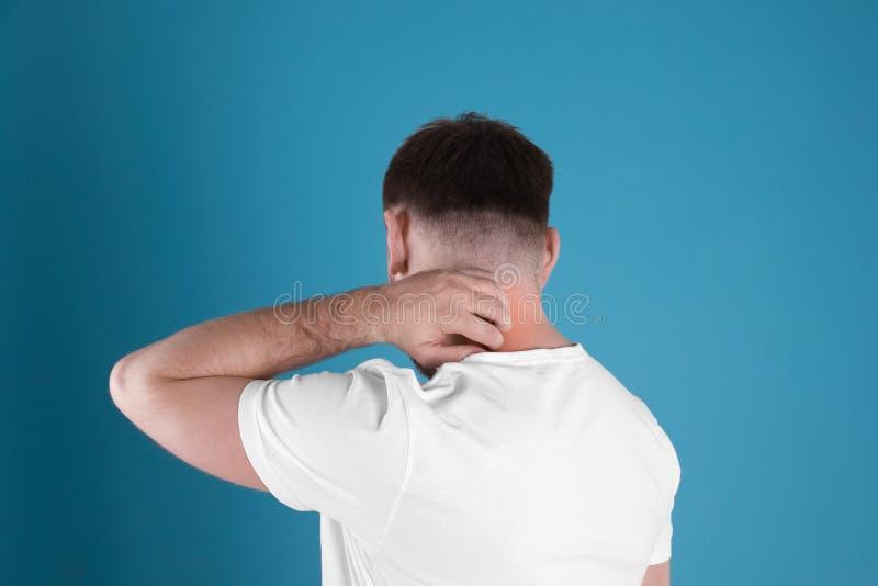 Человек царапая шею на предпосылке цвета стоковые фотографии rf