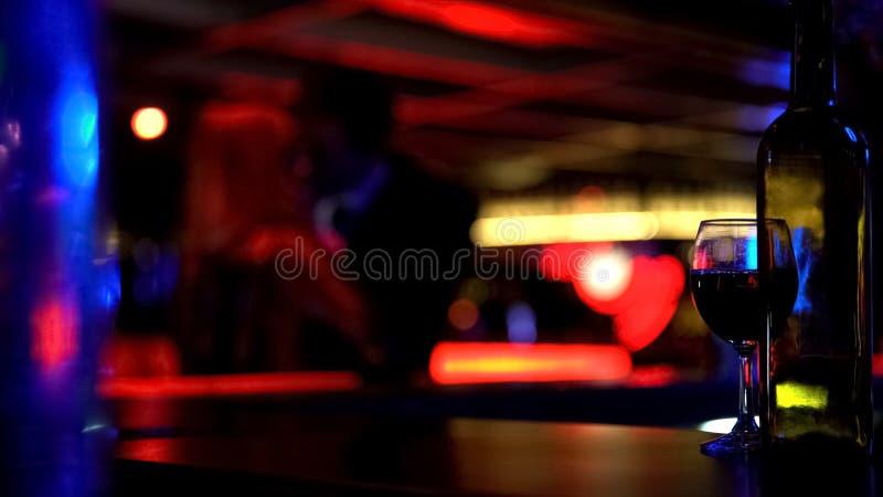 Человек целуя даму heartily на встрече, любовниках датируя в ночном клубе, defocused стоковая фотография rf