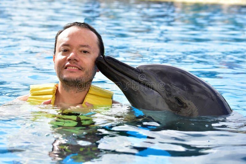 Человек целуя дельфина в бассейне стоковые изображения rf