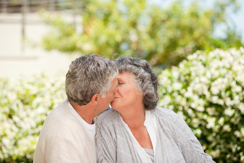 Человек целуя его супруги в саде стоковые изображения