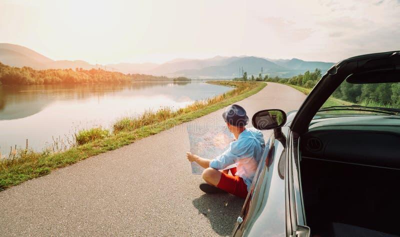 Человек читает дорожную карту сидя около его cabriolet на живописном mo стоковая фотография