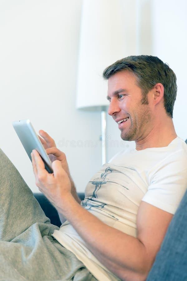 Человек читает Красную книгу, занимаясь серфингом с ПК таблетки стоковое фото