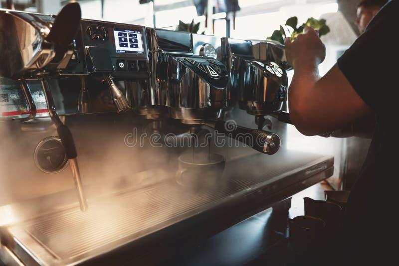 Человек Barista делая напиток кофе используя профессиональную машину кофе испаряясь вокруг в кафе стоковое изображение rf