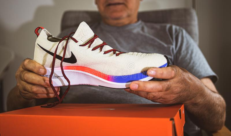 Человек Flyknit мухы сигнала Nike старший показывая новые ботинки стоковые фотографии rf