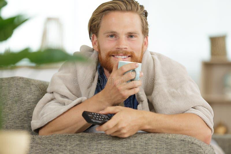 Человек Happ смотря ТВ пока держащ cuppa стоковые фотографии rf