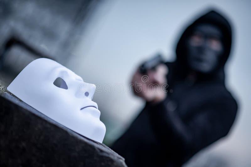 Человек hoodie тайны в черной маске указывая оружие на белую маску Концепции преступления и насилия стоковые фотографии rf
