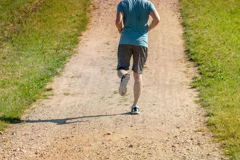 Человек jogging на сельской дороге стоковое фото rf