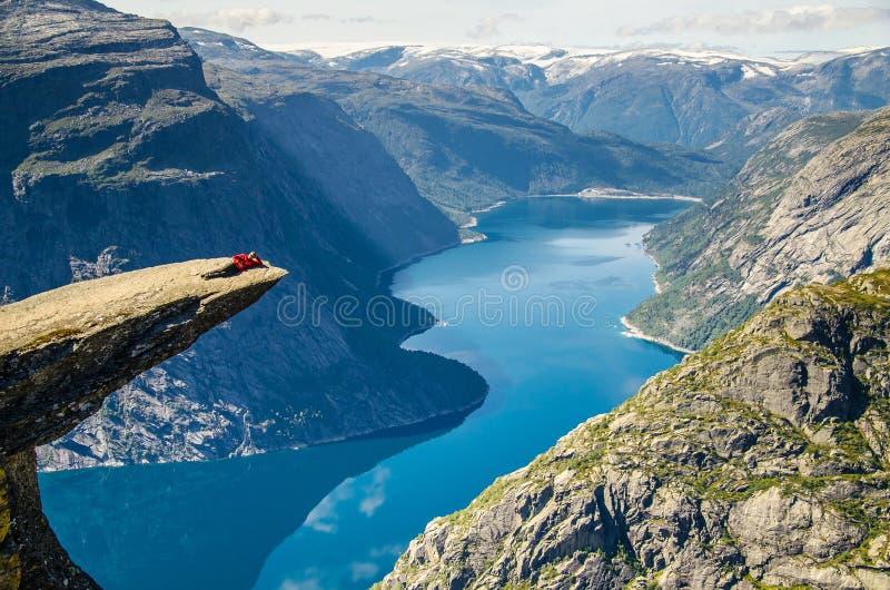 Человек l в красной куртке aying на утесе Trolltunga с голубым озером 700 метров более низко и интересного небо с облаками стоковые изображения