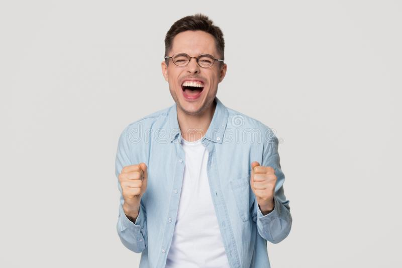 Человек Overjoyed возбужденный смешной молодой кричащий с утехой празднуя выигрыш стоковое фото