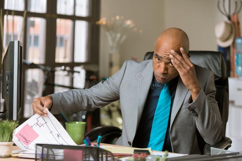 Человек Overworkedd в его офисе стоковое фото rf