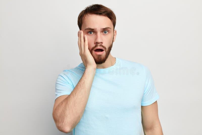 Человек Shocked возбужденный впечатленный с ладонью на его щеке, раскрыл рот в сюрпризе стоковое изображение