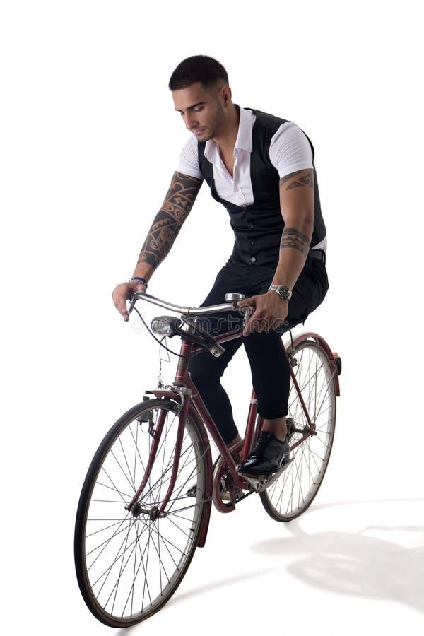 Человек Tattoed элегантный ехать его велосипед в istudio стоковое изображение