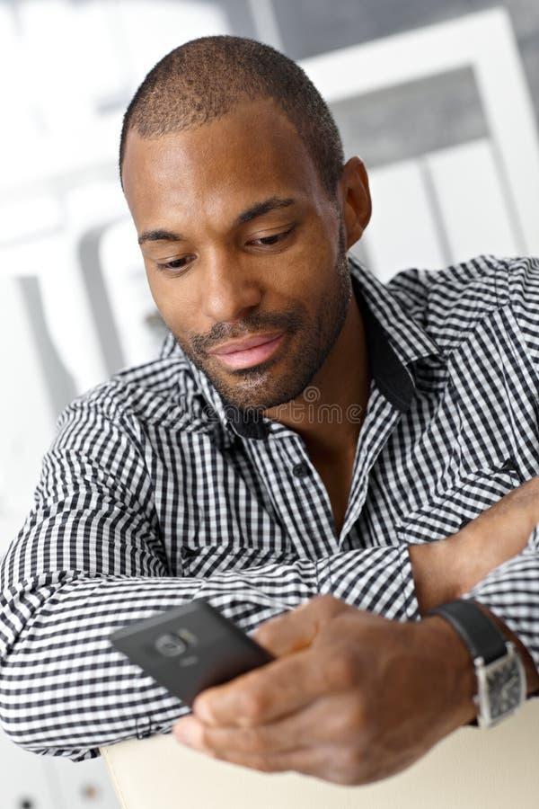 Человек texting на мобильном телефоне стоковая фотография