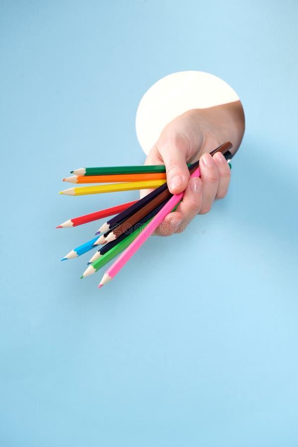 Человеческая рука выступая через отверстие в голубой предпосылке, держа покрашенный карандаш стоковая фотография