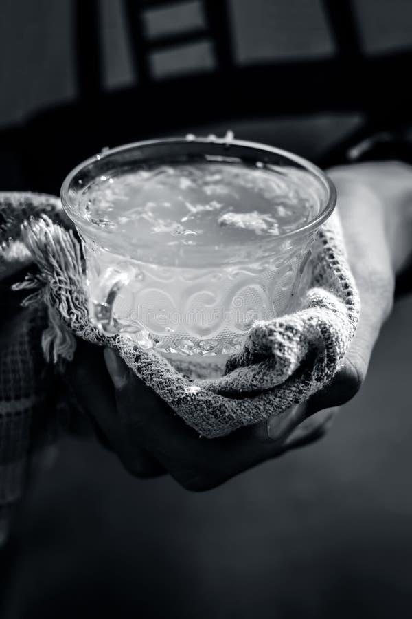 Человеческая рука держа белый лимон имбиря в его руке с полотенцем по мере того как оно горяче стоковые изображения rf