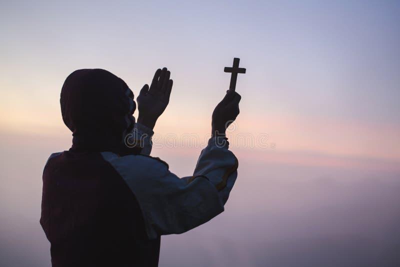 Человеческая рука держит крест и открытая ладонь вверх поклоняется Терапия евхаристии благословляет бога порция раскаивается като стоковая фотография rf