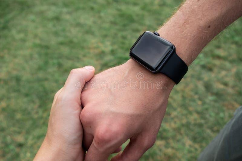 Человеческая рука нося умный вахту Пригодная для носки концепция устройства Пара держа руки closeup стоковая фотография rf